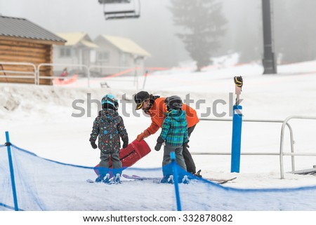 trainer teaching little boy and girl  how to mountain ski .