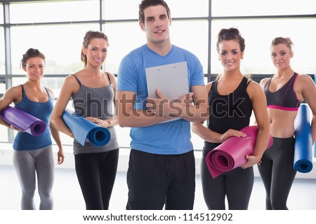 Trainer with his yoga class in gym
