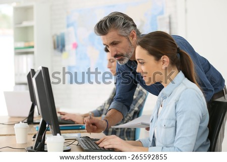 Trainer with student working on desktop computer stock photo