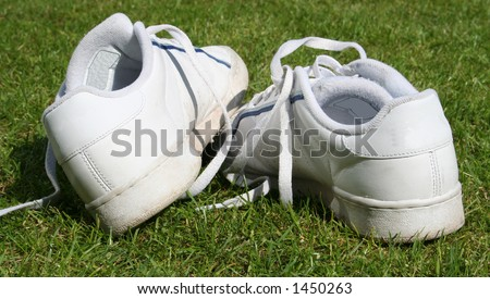 trainers, sneakers abandoned on grass background