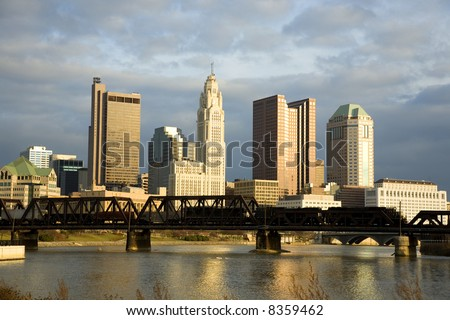 Traing crosses a bridge over the Scioto River with the skyline of Columbus, Ohio in the background at sunset - stock photo
