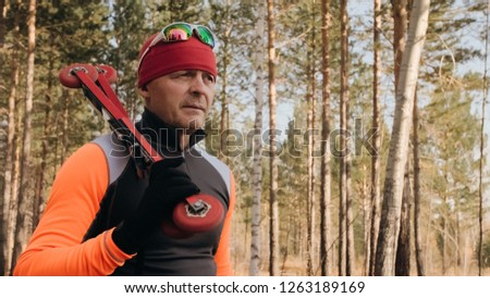 Training an athlete on the roller skaters. Biathlon ride on the roller skis with ski poles, in the helmet. Autumn workout. Roller sport. Adult man riding on skates.The athlete goes and holds sports #1263189169