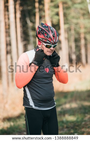 Training an athlete on the roller skaters. Biathlon ride on the roller skis with ski poles, in the helmet. Autumn workout. Roller sport. Adult man riding on skates. Athlete is getting ready to start. #1388888849