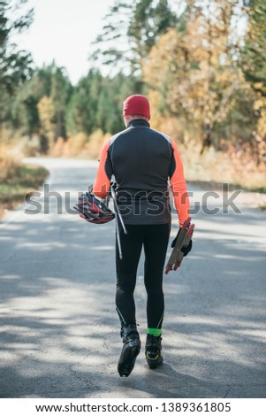 Training an athlete on the roller skaters. Biathlon ride on the roller skis with ski poles, in the helmet. Autumn workout. Roller sport. Adult man riding on skates. #1389361805
