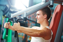 training and bodybuilding. man doing excersizes on training machine in gym