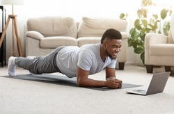 Training At Home. Sporty man doing yoga plank while watching online tutorial on laptop, exercising in living room, free space