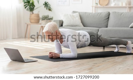 Training At Home. Sporty senior woman doing yoga plank while watching online tutorial on laptop, exercising in living room, free space, panorama