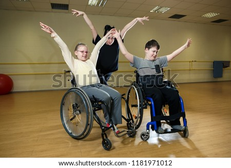 Training for dance competition of inclusive dance of handicapped children on wheelhairs with trainers in sport hall in Estonia, optimism and desire to act #1181971012