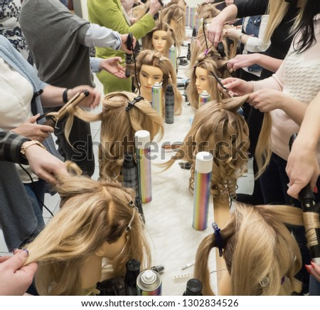 Training hairstyles on the mannequin. Teamwork. Close up #1302834526