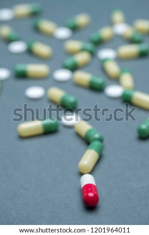 Training of random capsules white and green isolated on a blue background, conceptual image, conceptual image