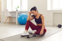 Training on isolation. Slightly tired smiling woman resting after an active fitness workout sitting on a sports mat in the room. Athlete does not miss training while at home in self-isolation.