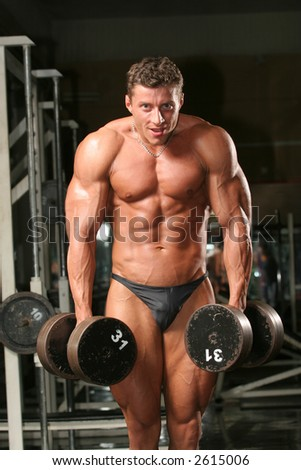 training shot of a young man in the gym, dumbbell, shrugs