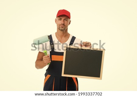 Training that transforms beginner into skilled professional. Painter hold blackboard and paint roller. Decorator training course. Training school. Training in painting and decorating, copy space Stock photo ©
