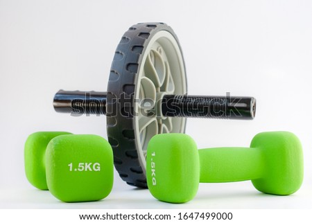 Training tools ab wheel and dumbells green colored. Conception of body building on white background.