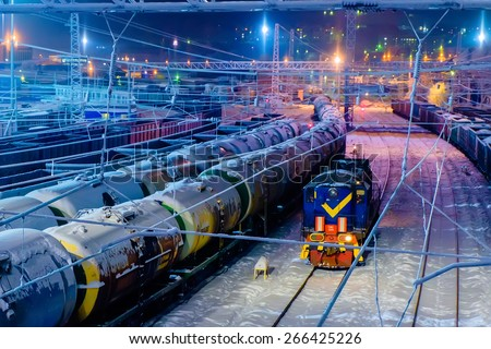 Trains of oil tanks and wagons on the cargo railway station at winter night