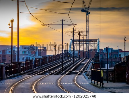 Tram and tramlines in central Manchester, UK, with setting sun and clouds.