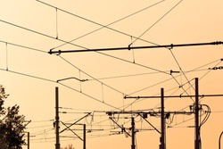 Tram  cables at sundown.Tramway overhead traction photo. Electric, transport wires photography.  Transportation infrastructure at sunset in downtown . Urban traffic wire structure.