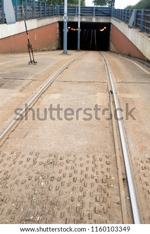 Tram lines running down a road and into a tunnel in the city #1160103349