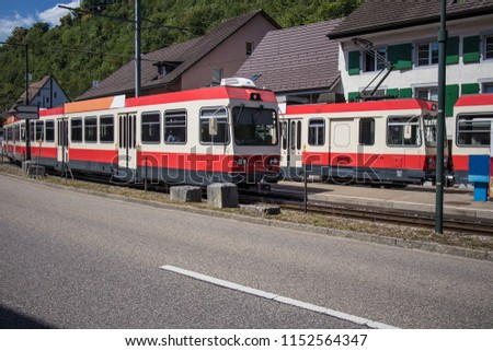 Tram station in the town of Holstein, a part of Switzerland close to Basel. side view of tracks occupied with two local trams in red and white color. #1152564347