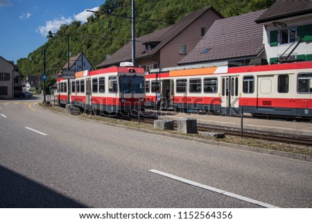 Tram station in the town of Holstein, a part of Switzerland close to Basel. side view of tracks occupied with two local trams in red and white color. #1152564356