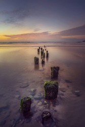 Tramore Beach, Waterford, Ireland. View of the reflections of the stones and woods in the water at low tide and the long pier at sunset or sunrise hours