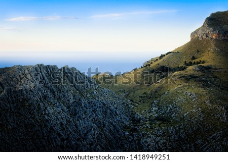 Tramuntana mountain region located near Sa Calobra. Lone house in the distance at sunset with rocks, green pastures, mediterranean sea and blue sky, Mallorca, Spain.