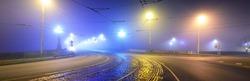 Tramway track and asphalt road (highway) through the illuminated empty Stone bridge in a thick fog at night. Lanterns close-up. Daugava river, Riga, Latvia. Concept image, neon colors
