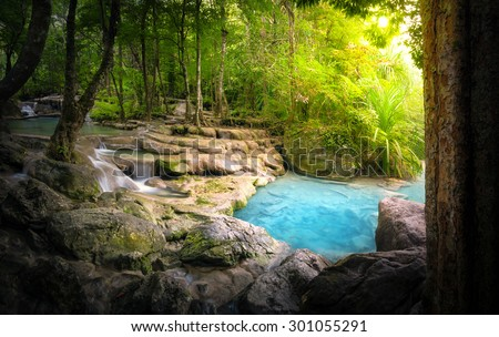 Tranquil and peaceful nature background of beautiful river stream flowing through natural cascades and wet stones with sunlight shining gently