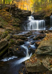 tranquil and serene cascading waterfalls and autumn foliage trees in Ricketts Glenn in Pennsylvania.