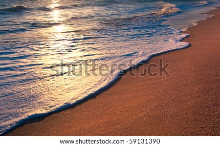 Tranquil beach sunrise. Sea waves foam and golden sand. Copyspace background. - stock photo