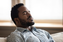 Tranquil calm young african american man resting with eyes closed taking deep breath of fresh air enjoy comfort relaxing on couch feel peace mind and stress relief meditate at quiet home sit on sofa
