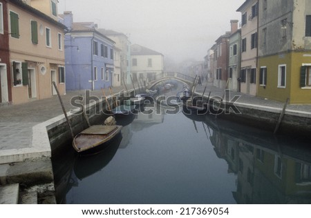 Tranquil canal streetscape in Burano, Venice, Italy #217369054