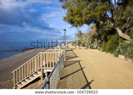 Tranquil footpath with stairs to the beach by the Mediterranean Sea between Marbella and Puerto Banus (on the horizon) in Andalucia region, southern Spain.
