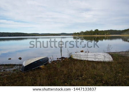 Tranquil Lake Scene with two upturned Dinghies tied up ashore