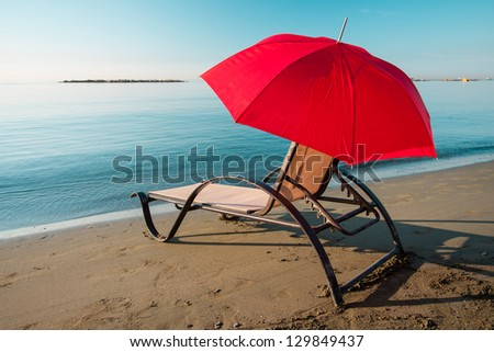 Tranquil Mediterranean morning beach with red umbrella and chair