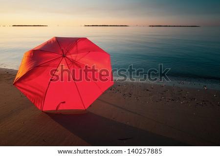 Tranquil Mediterranean morning seashore with beach umbrella