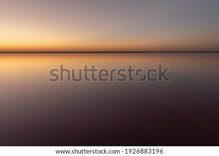 Tranquil minimalist landscape with smooth surface of the pink salt lake with calm water with horizon with clear sky in sunset time. Simple beautiful natural calm background ストックフォト ©