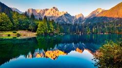 Tranquil morning scene of Fusine lake. Captivating summer sunrise in Julian Alps with Mangart peak on background, Province of Udine, Italy, Europe. Beauty of nature concept background.