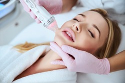 Tranquil patient being treated using a fractional radio frequency microneedle machine with a vacuum suction
