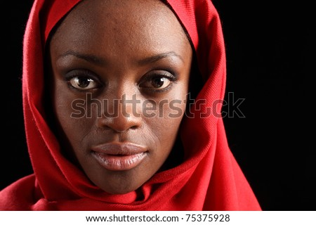 Tranquil portrait of beautiful young black african american woman wearing red hijab, taken against a black background.