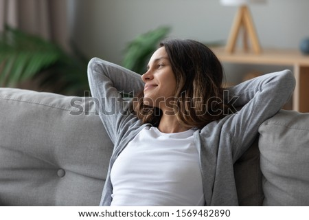 Tranquil pretty woman in casual home clothes put hands behind head leaned on couch resting in living room looking away smiling feeling serenity. Take break, keep calm, mood and free lazy time concept