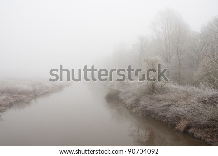 Tranquil scene as partially frozen river flows away into misty landscape on winter day in rural Shropshire. #90704092
