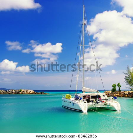 tranquil scene in sunny morning on Seychelles with sailing boat