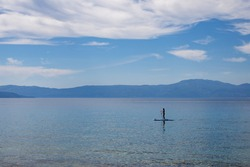 Tranquil scene of a stand-up paddle boarder on the coast of a Croatian island. Blue ocean, blue sky and some picturesque clouds.
