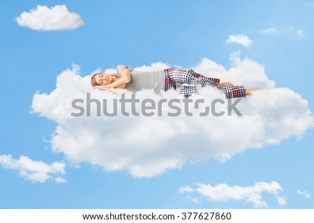 Stock Photo Tranquil scene of a young woman dreaming and sleeping on a cloud up in the sky