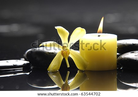 tranquil spa scene - aromatherapy candle and yellow orchid zen stones