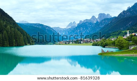 Tranquil summer Italian dolomites mountain lake and village view (Auronzo di Cadore). Four shots composite image.