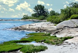 Tranquil summer scene in coastal Maine. View of small sand beach and huge granite boulders along rugged shoreline of Clark Island in mid-coast Maine.