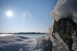 Tranquil wintertime scene with a close-up to rocks covered with ice and snow and ice-free river in background on a sunny spring day. The beginning of March. Horizontal photographic image.
