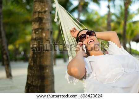 Tranquil woman relaxing lying on a hammock at tropical beach. Summer vacation relax and tranquility concept. Relaxed female resting outdoor. Riviera Maya, Mexico. #606420824
